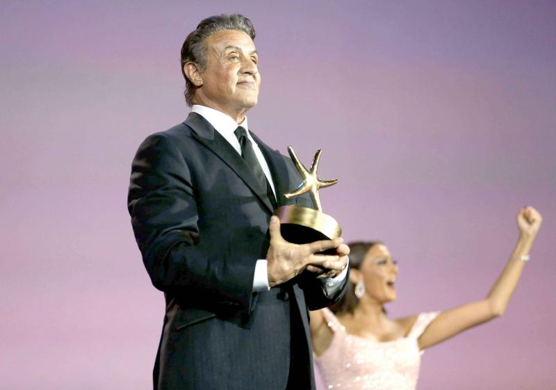 Egyptian-actress-Buhra-Rozza-R-reacts-as-American-actor-and-director-Sylvester-Stallone-poses-with-his-Career-Achievement-Award-at-the-El-Gouna-film-festival-on-September-28-2018.